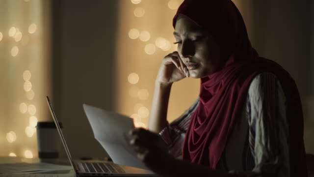 close up of woman wearing hijab with headache typing on laptop at night and reading paperwork / cedar hills, utah, united states - nahöstlicher abstammung stock-videos und b-roll-filmmaterial