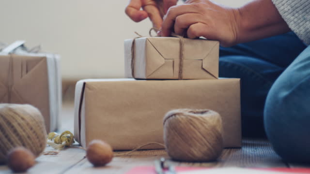 close up of woman wrapping christmas presents at home. workshop at home during covid-19 reality. the new normal. - gift box stock videos & royalty-free footage