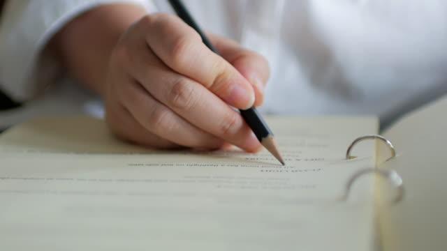 närbild på kvinna skriver på anteckningar med en penna, arbetar hemma - underskrift bildbanksvideor och videomaterial från bakom kulisserna