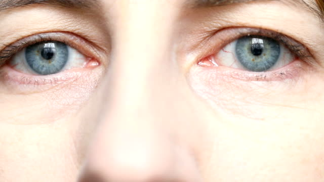 close up of woman's blue eyes - only mature women stock videos and b-roll footage