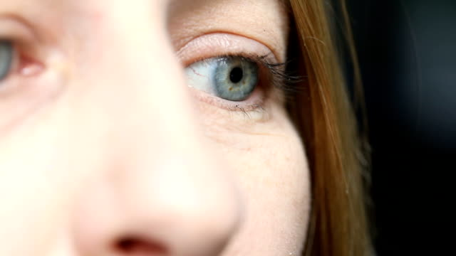 close up of woman's eye in conversation - blue eyes stock videos and b-roll footage