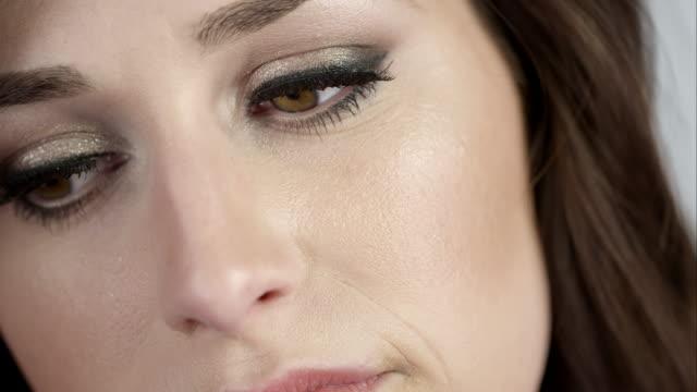 close up of woman's face as she tilts head. - オレム点の映像素材/bロール