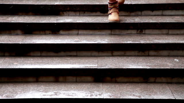 Close up of woman's feet walking down the marble stairs