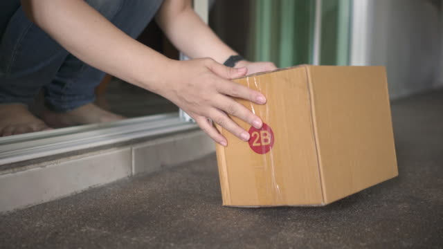close up of woman's hand collecting a delivered package from her doorstep at home. shipping and delivery concept. - doorstep stock videos & royalty-free footage
