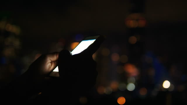 close up of woman's hand while playing game and surfing internet by using smart phone with bokeh background-night life with leisure activity - game night leisure activity stock videos & royalty-free footage