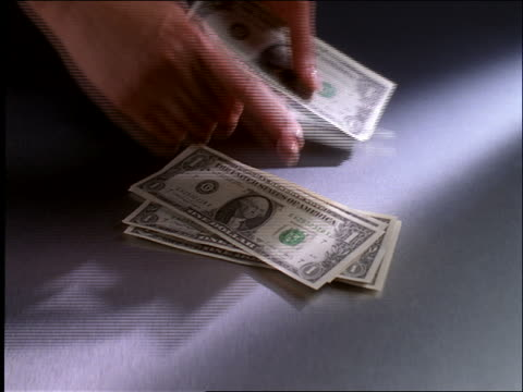 close up of woman's hands counting US dollar bills