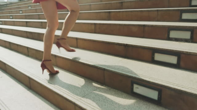 vídeos de stock e filmes b-roll de close up of woman's legs stepping up on stairway in city - stock video - degraus
