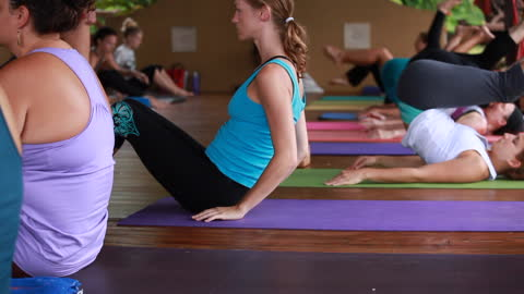 close up of women hugging her shins in and then many women in the yoga class rolling back-and-forth on their backs on their yoga mats with the teacher walking in the middle of the room and more women in yoga attire in the background on a yoga deck - kelly mason videos stock videos & royalty-free footage