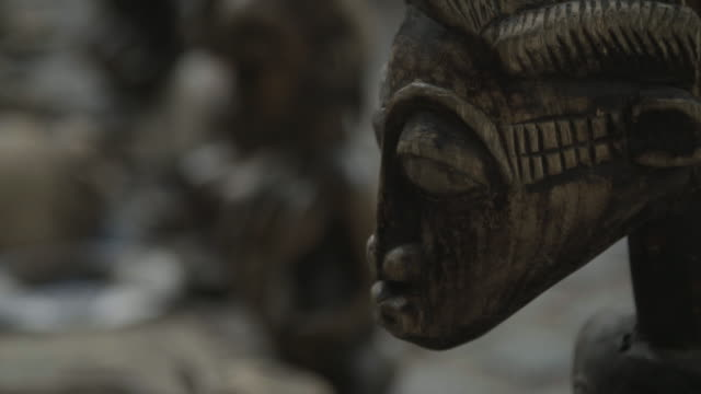 vidéos et rushes de close up of wooden african dolls, rack focus - sculpture produit artisanal