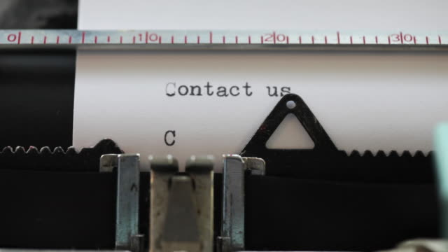 close up of words being typed on old typewriter: 'contact us..' repeated - タイプライター点の映像素材/bロール