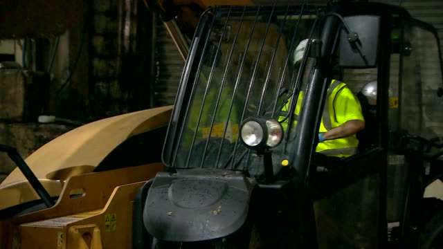 Close up of worker operating digger in recycling plant