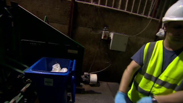 Close up of workers loading blue wheelie bins into reprocessing plant