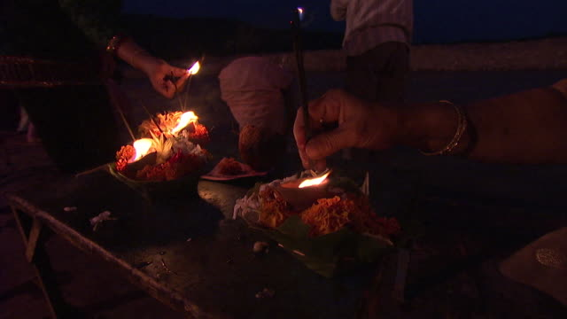 Close up of worshippers ligting incense and candle offerings in India