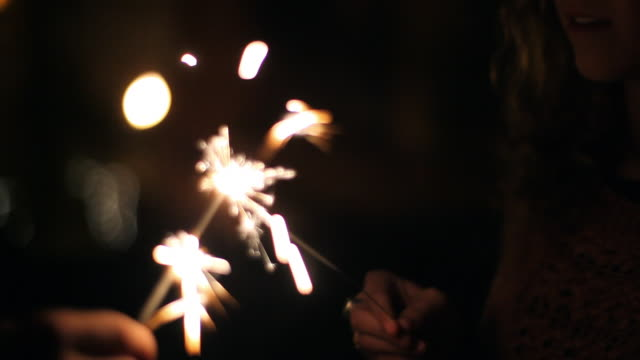 Close up of young adult female girlfriend lighting sparkler