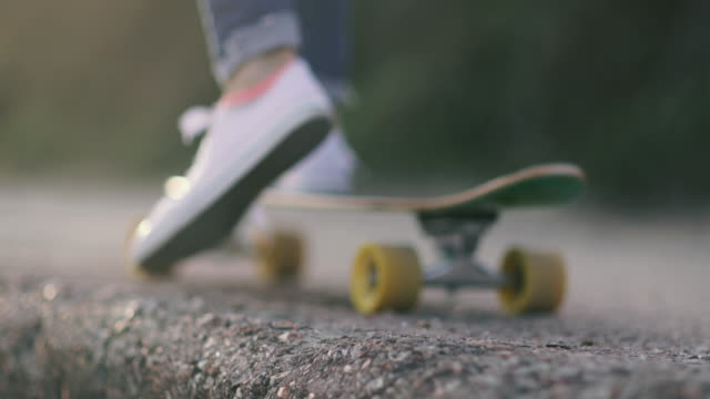Close up of young adult female skateboarding at sunset