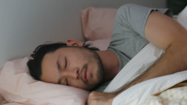 close up of young asian man bad sleep, insomnia lying on bed - cuscino biancheria da letto video stock e b–roll