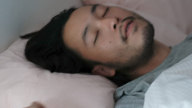 close up of  young asian man deep sleeping with comfortable in bed - duvet stock videos & royalty-free footage