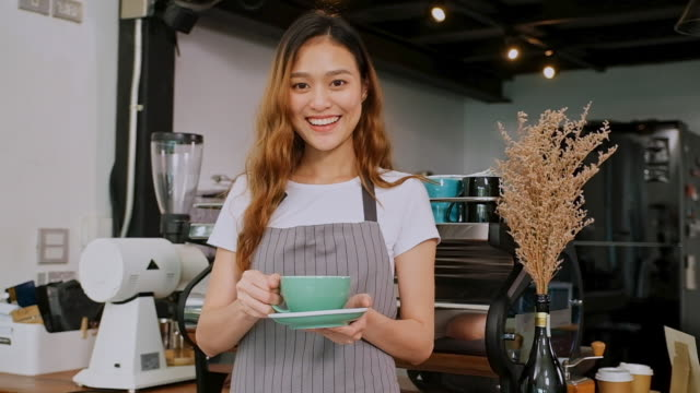 close up of young asian woman barista holding coffee cup, smiling and looking at camera while standing at counter in coffee shop cafe, slow motion - giving stock videos & royalty-free footage
