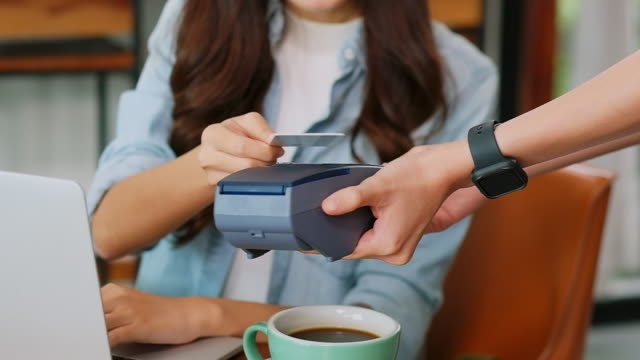 close up of  young asian woman customer hand making contactless payment through smart phone with waitress hand holding credit card reading machine to service costumer at table in cafe, slow motion - tapping stock videos & royalty-free footage