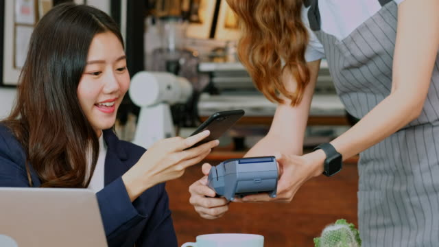 close up of  young asian woman customer making conractless payment through smart phone with waitress hand holding credit card reading machine to service costumer at table in cafe - tap stock videos & royalty-free footage