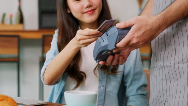 close up of young asian woman customer making contactless payment through credit card with waiter hand holding credit card reading machine to service costumer at table in cafe, slow motion - day stock videos & royalty-free footage