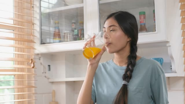 close up of young beautiful asian woman drinking orange juice in kitchen, healthy lifestyles - detox stock videos & royalty-free footage