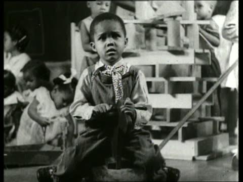 B/W close up of young black boy on rocking horse /nursery school / SOUND