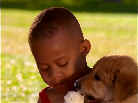 close up of young black boy with puppy eating ice cream cone