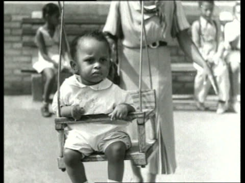 b/w close up of young black child being pushed on swing / playground / sound - single mother stock videos & royalty-free footage