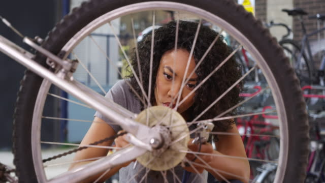 vidéos et rushes de close up of young black woman working on bicycle in alley behind bike shop - fracture