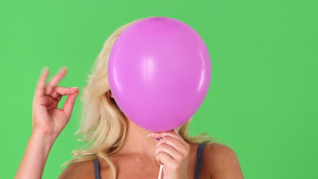 close up of young blonde woman and pink helium balloon popping - ヘッドショット点の映像素材/bロール