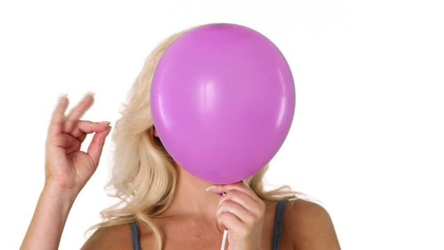 close up of young blonde woman and pink helium balloon popping - balloon stock videos and b-roll footage