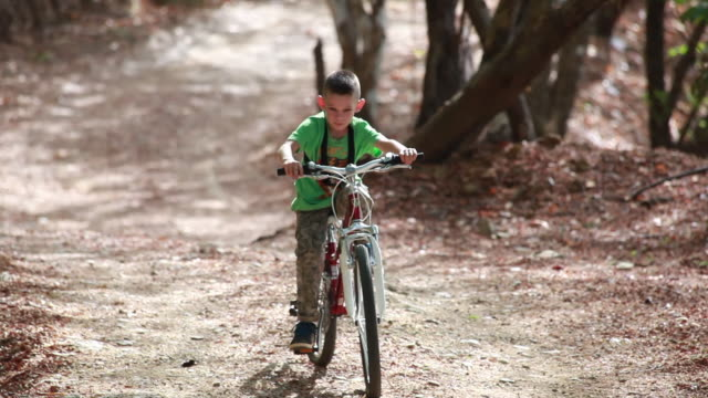 vidéos et rushes de close up of young boy riding a bicycle on a country road in the jungle with gopro harness - kelly mason videos