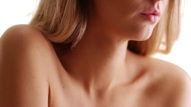 close up of young caucasian woman's neck and bare shoulders on white background - 肩点の映像素材/bロール