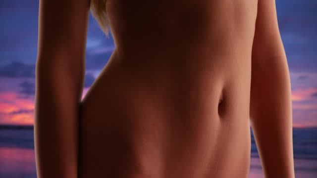 close up of young caucasian woman's stomach and arms on the beach at sunset - navel stock videos & royalty-free footage
