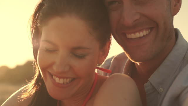 close up of young couple laughing on beach in sunset. - 30多歲 個影片檔及 b 捲影像