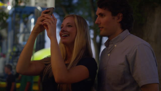 stockvideo's en b-roll-footage met close up of young couple videoing with cell phone at carnival / american fork, utah, united states - videoportret