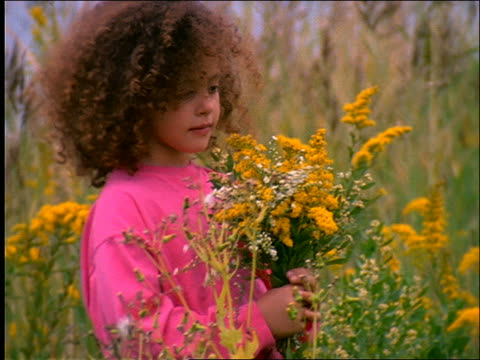 close up of young girl carrying flowers in field of wildflowers / Connecticut