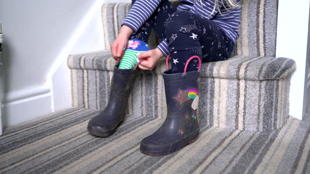 close up of young girl pulling on rubber boots on stairs - children only stock videos & royalty-free footage