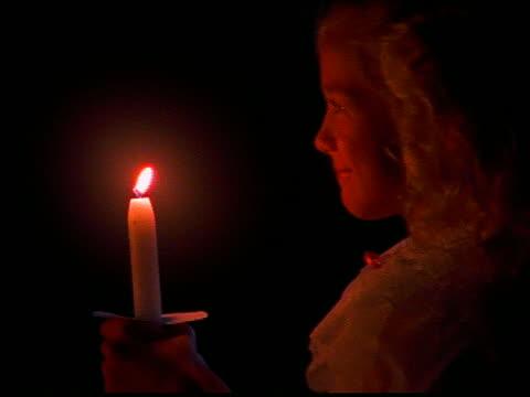 vidéos et rushes de close up of young girl walking carrying lit candle at night - seulement des petites filles