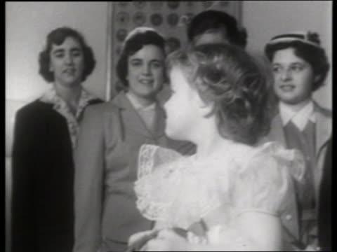 vidéos et rushes de b/w close up of young girl with flowers / women in background / no - seulement des petites filles