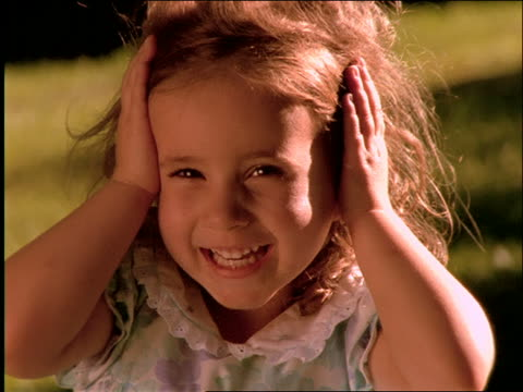 stockvideo's en b-roll-footage met close up of young girl with hands on head smiling outdoors - alleen meisjes