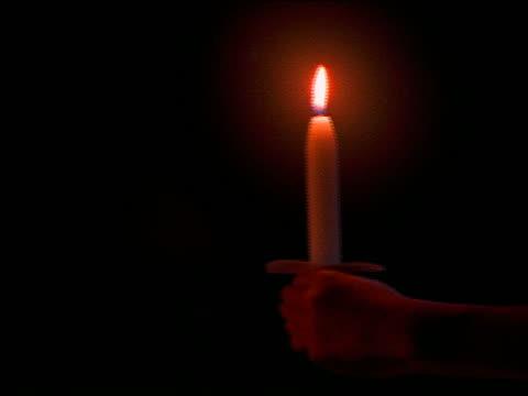 vidéos et rushes de close up of young girl's hands holding lit candle / tilt up to face / night - seulement des petites filles