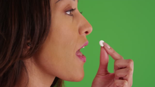 vidéos et rushes de close up of young latina woman taking pill then drinking water on green screen - drinking health 1930 film