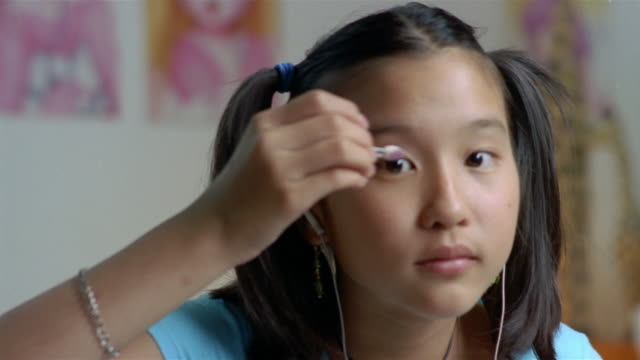 close up of young teenage girl applying eye shadow while listening to music on earphones - 14歳から15歳点の映像素材/bロール