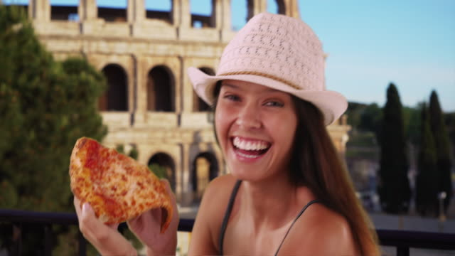 Close up of young tourist woman near the Roman Colosseum eating pizza