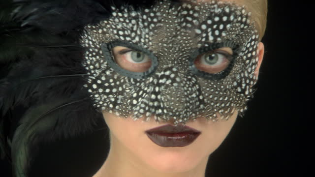 Close up of young woman in a feather mask turning to camera