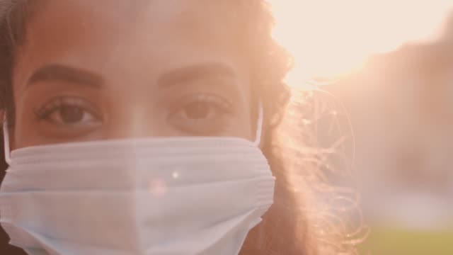 close up of young woman in protective face mask smiling at camera - removing stock videos & royalty-free footage