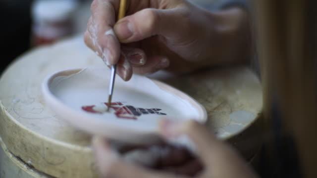 vidéos et rushes de fermez-vous vers le haut de la jeune femme effectuant la céramique de noel dans son atelier de poterie, concept de petite entreprise - décoration de fête