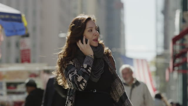 Close up of young woman talking on cell phone in city / New York City, New York, United States
